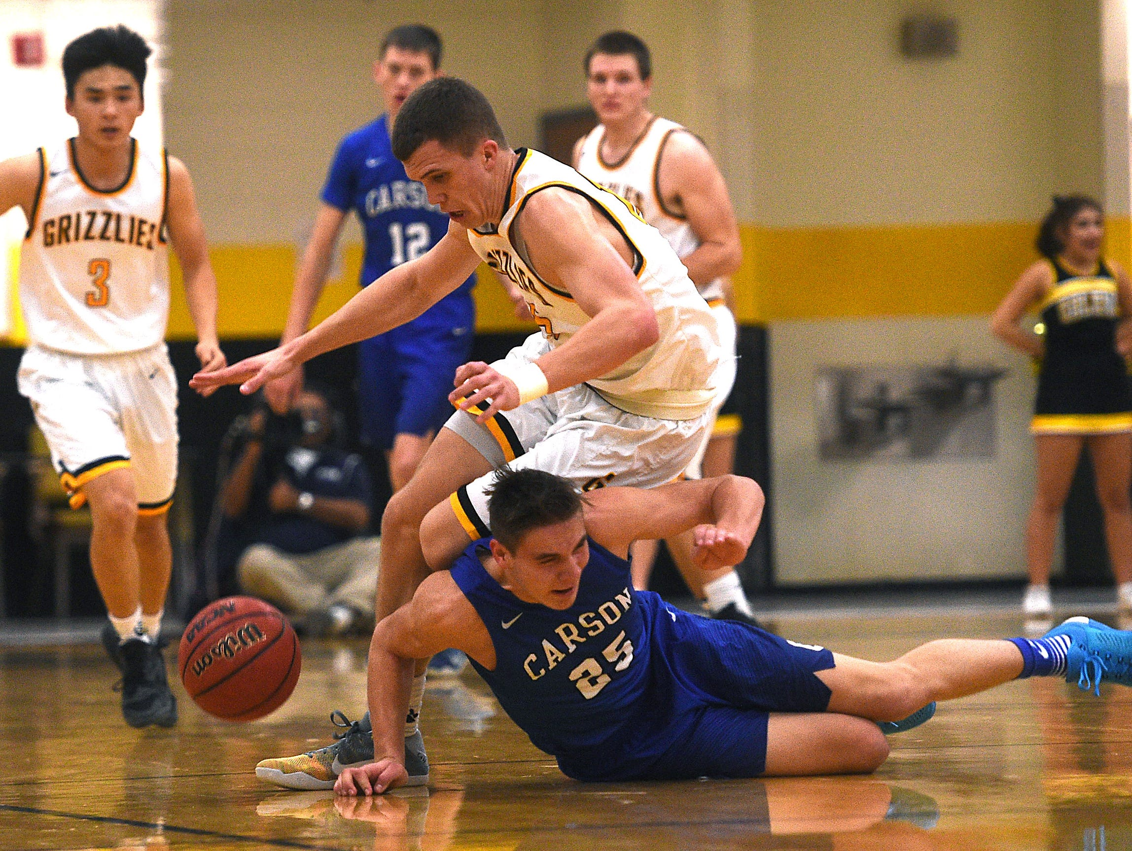 Galena's Dillon Voyles (15) battles Carson's Jayden Dejoseph (25) for a loose ball during their basketball game at Galena on Friday