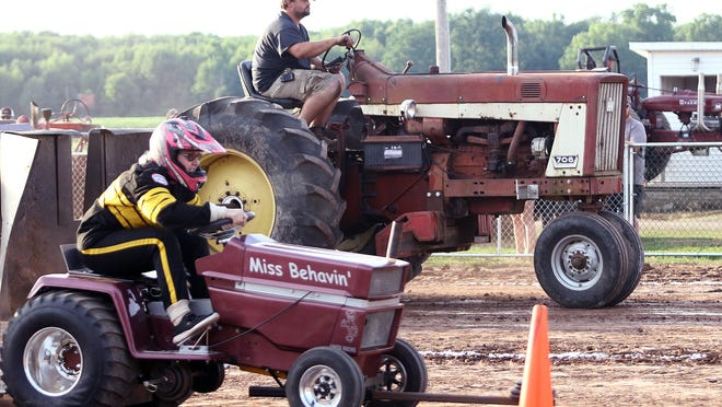 A quarter scale garden tractor, left, and a stock tractor carry on their respective pull attempts Saturday during the second night of tractor pull competition at the Mile Branch Grange.