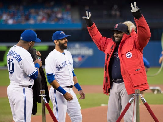 Boston Red Sox designated hitter David Ortiz, right, tries on a Canada Goose winter jacket that was given to him as a gift by Toronto Blue Jays right fielder Jose Bautista, center, and designated hitter Edwin Encarnacion before a baseball action in Toronto, Friday, Sept. 9, 2016. (Peter Power/The Canadian Press via AP)