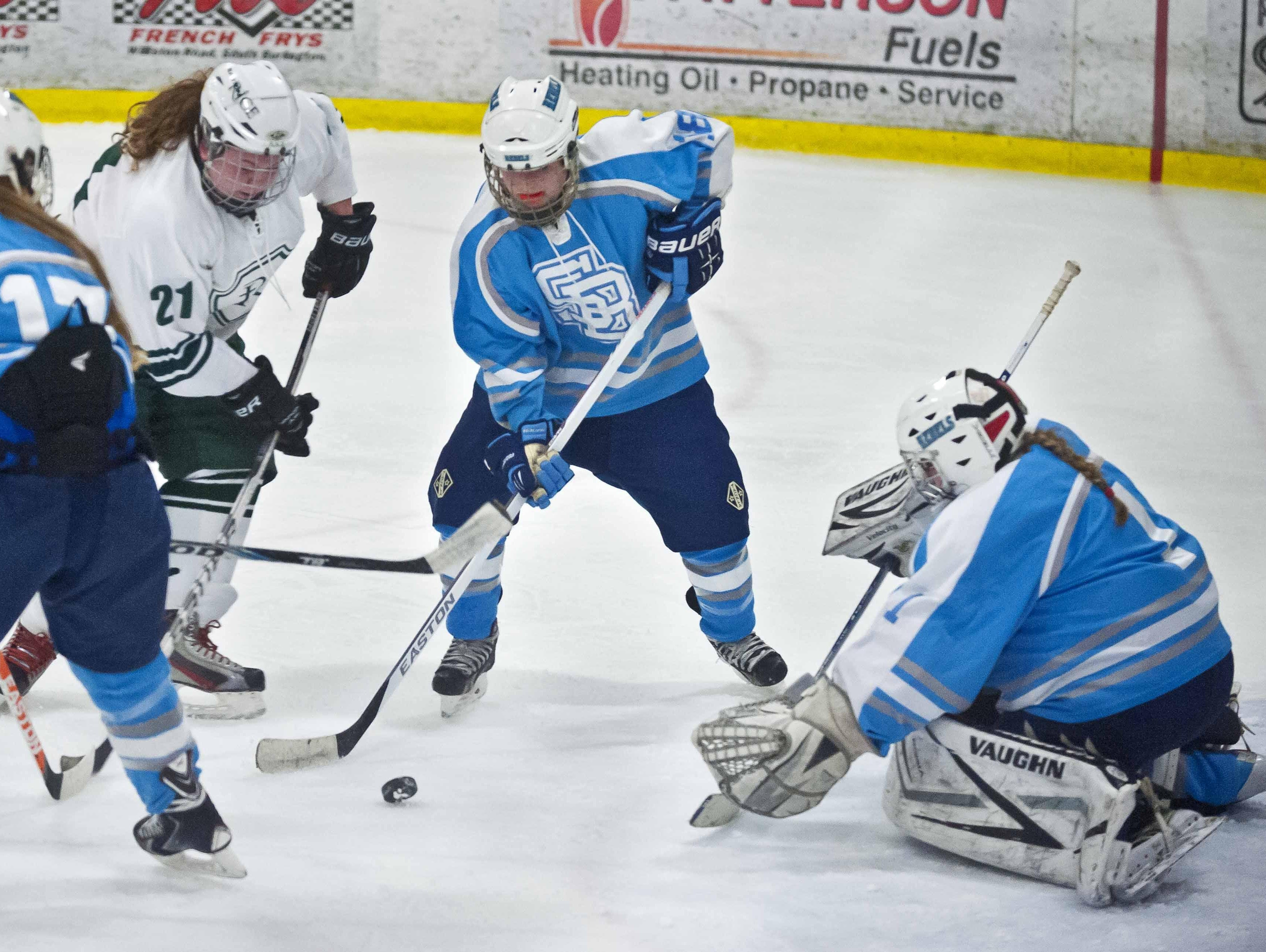 South Burlington's Casey Johnson (center) and Rice Memorial's Dempsey Cronan contest the puck in front of Rebel goalie Erin Church during a game last season.