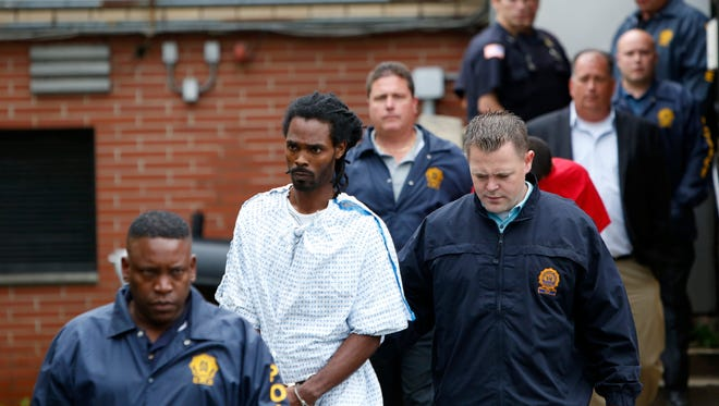 Taqiy A. Walton, one of the two men facing attempted murder charges in the shooting of a retired police officer, is escorted to Greenburgh Town Court July 14, 2015. Retired police officer Peter Schmidt Sr. was shot when he interrupted a burglary at his neighborÕs house.