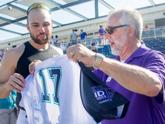 Alzheimer's Association representative Brian LeBlanc, right, gets Eric Jagielo's jersey after the Mobile BayBears vs. Blue Wahoos baseball game at Blue Wahoos Stadium in Pensacola, FL on Sunday, June 17, 2016.  LeBlanc had the winning bid for Jagielo's throw-back Pelicans #17 jersey; Jagielo happen to have the walk off hit to win the game.  All of the players' jerseys were auctioned off to raise money for the Alzheimer's Association.