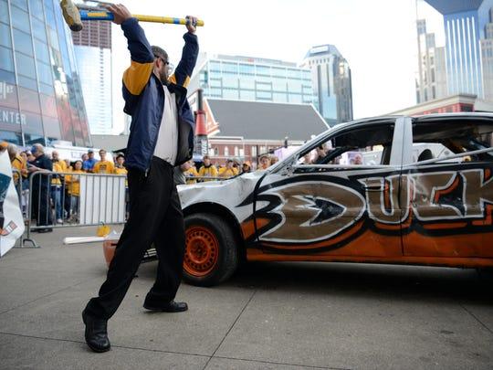 Michael Cornish hits a Ducks car with a sledge hammer