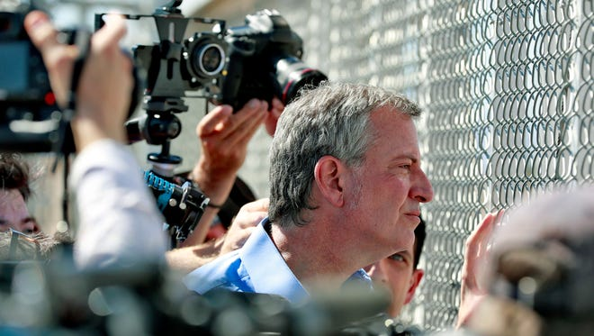 In this Thursday, June 21, 2018, file photo, New York City Mayor Bill de Blasio looks through a closed gate at the Port of Entry facility, in Fabens, Texas, where tent shelters are being used to house separated family members.
