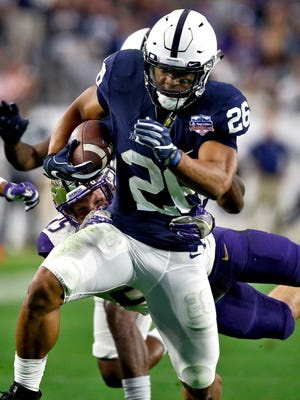 Penn State running back Saquon Barkley (26) carries as Washington linebacker Ben Burr-Kirven reaches for a tackle during the second half of the Fiesta Bowl NCAA college football game Saturday, Dec. 30, 2017, in Glendale, Ariz. (AP Photo/Ross D. Franklin)