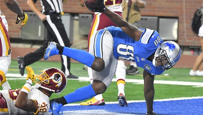 Lions' Anquan Boldin takes the football with him after scoring the winning touchdown late in the fourth quarter.