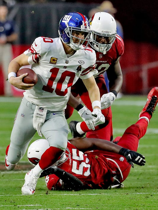 New York Giants quarterback Eli Manning (10) is tripped up by Arizona Cardinals outside linebacker Chandler Jones (55) during the second half of an NFL football game, Sunday, Dec. 24, 2017, in Glendale, Ariz. (AP Photo/Rick Scuteri)