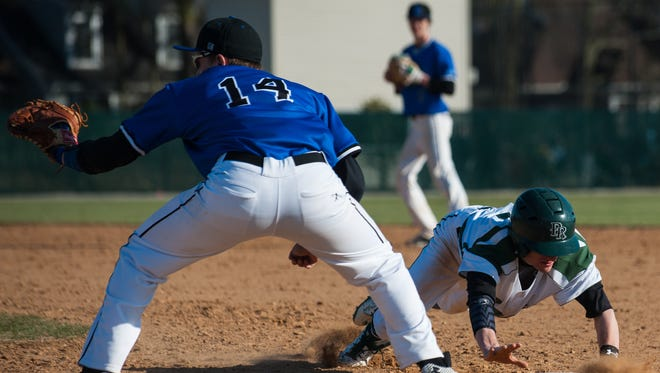 Parkside Colin Green (5) slides back to first before the tag by Stephen Decatur first baseman Tristan McDonough (14) at Parkside High School on Tuesday afternoon in Bayside South action.