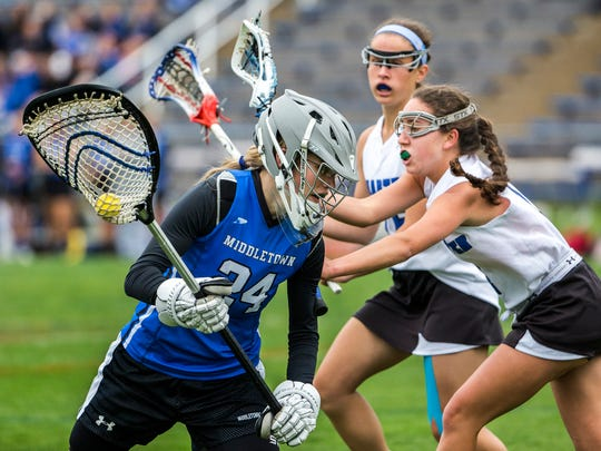 Middletown goalie Mauri Hainsworth tries to escape a pair of Charter attackers in the first half of Charter's 15-2 win over Middletown at Charter School of Wilmington on Thursday afternoon.