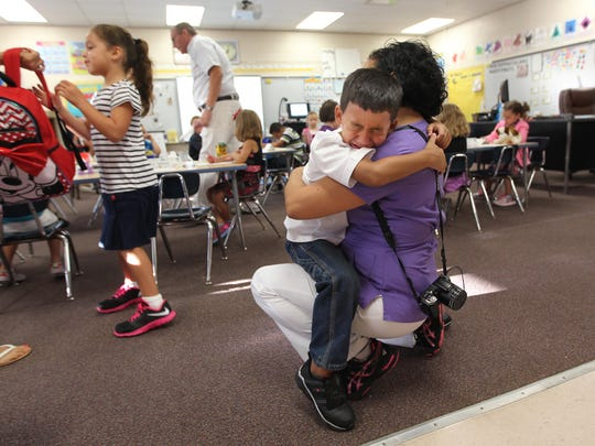 Three Oaks Elementary kindergartner Bradley Lawson, 5, clings tight to mom Fabiola as she tries to leave Monday, Aug. 24, the first day of classes for all Lee County Schools.