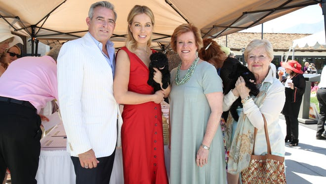 (left to right) Event Co-chair Patrick Mundt, Event Co-chair Tristan Milanovich, (holding one of the eight-week-old Guide Dog puppies) Executive Director of Guide Dogs of the Desert Sarah G. Clapp, and Event Host Yvonne Maloney (holding another one of those puppies).