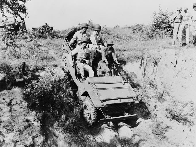 West Point cadets and a U.S. Army soldier drive a Jeep