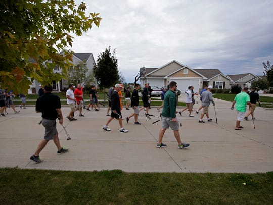 Neighbors and friends bring their golf clubs as they