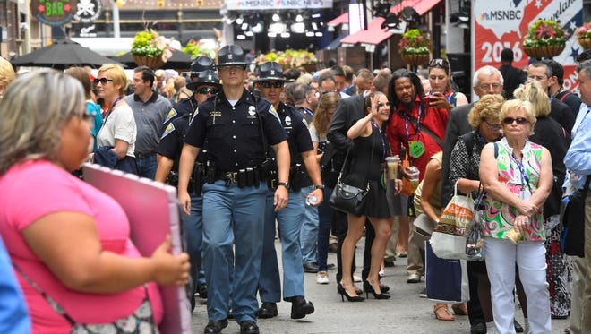 Long lines form after security pushed people away from a parking lot and a security screening location outside of Quicken Loans Arena along Huron Street on the first day of events during the 2016 Republican National Convention at Quicken Loans Arena.