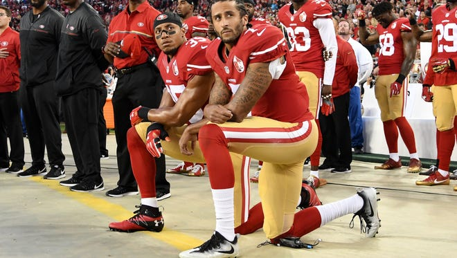Colin Kaepernick #7 and Eric Reid #35 of the San Francisco 49ers kneel in protest during the national anthem prior to playing the Los Angeles Rams in their NFL game at Levi's Stadium on September 12, 2016 in Santa Clara, California.