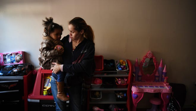 Yanira Cortes, 28 of Newark, with her daughter Brielle, 2, at their apartment at Pueblo City on Monday, Nov. 14, 2016.  Yanira Cortes, 28 of Newark, with her daughter Brielle, 2, at their apartment at Pueblo City on Monday, Nov. 14, 2016.  Pueblo City, has been condemned in the past and Cortes and her family live in substandard conditions. At time of photo her electricity was off.   88774636