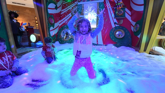 """Let it snow! Lilly Restaino, 7, plays in the """"snow""""  with 4-year-old Gianni and 2-year-old Matteo Zanlout at the Short Hills Mall in New Jersey on Nov. 8."""