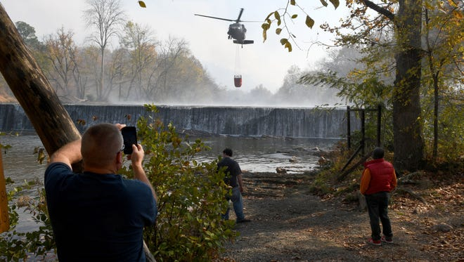 A Air National Guard helicopter getting water from the Little River making drops along the fire lines burning was quite the tourist attraction Friday, Nov. 18, 2016.