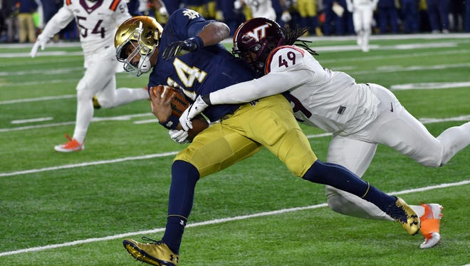 Nov 19, 2016; South Bend, IN, USA; Notre Dame Fighting Irish quarterback DeShone Kizer (14) is tackled by Virginia Tech Hokies linebacker Tremaine Edmunds (49) in the third quarter at Notre Dame Stadium. Virginia Tech won 34-31. Mandatory Credit: Matt Cashore-USA TODAY Sports
