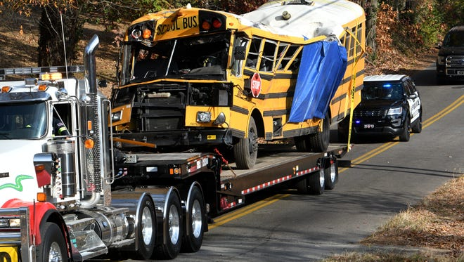 Chattanooga Police vehicles escort a flatbed truck hauling a crushed school bus from the scene on Talley Road in Chattanooga on Nov. 22, 2016. At least six Woodmore Elementary School students were killed when the bus crashed Nov. 21.
