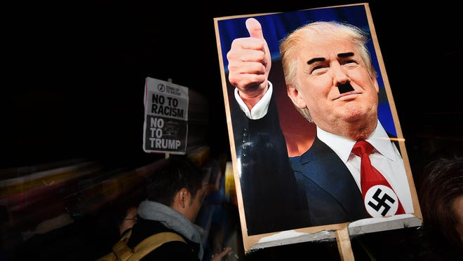 A demonstrator holds a placard showing a picture of US President-elect Donald Trump modified to add a swastika and an Adolf Hitler-style moustache during a protest outside the US Embassy in London November 9, 2016 against Trump after he was declared the winner of the US presidential election.  Political novice and former reality TV star Donald Trump has defeated Hillary Clinton to take the US presidency, stunning America and the world in an explosive upset fueled by a wave of grassroots anger. / AFP / BEN STANSALL        (Photo credit should read BEN STANSALL/AFP/Getty Images)