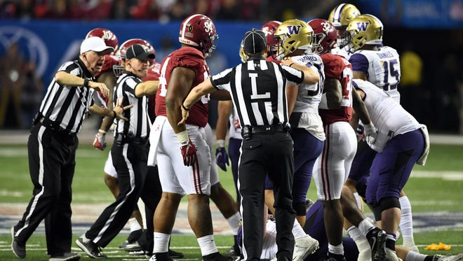 Officials break up a skirmish between Alabama and Washington players late in the fourth quarter.