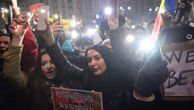 Protesters turn on their cellphone lights as they protest in front of the government headquarters against the government's contentious corruption decree in Bucharest, Romania on Feb. 5, 2017.