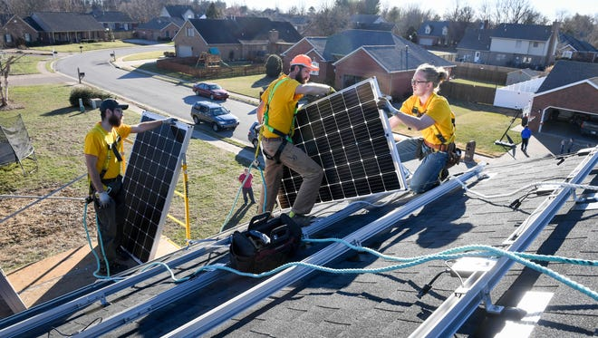 Solar panel installers place new panels on the roof of a home in Newburgh, Indiana in 2017.