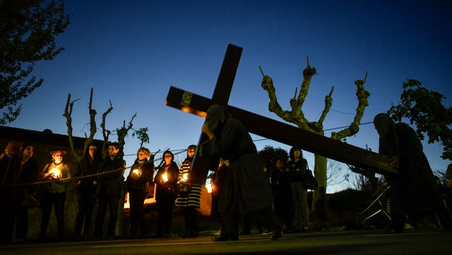 A penitent carries a cross taking part in the procession of ''El Ensogado'' during the Holy Week in Sietamo , northern Spain, Thursday.