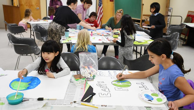 (right) Meline Tarpinyan, 10, and ( left) Hesoo Kang, 6, make signs at the Leonia Public Library on Saturday, April 22, 2017, for the Leonia Climate March.