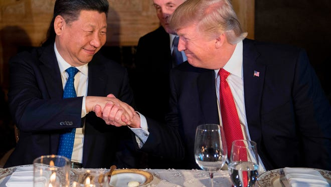 President Donald Trump, right, and Chinese President Xi Jinping, left, shake hands in April during dinner at the Mar-a-Lago estate in West Palm Beach, Fla.