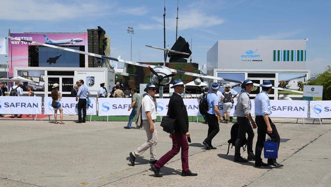 People walk by a Safran Electronics and Defense surveillance drone displayed at the International Paris Air Show on June 20, 2017.