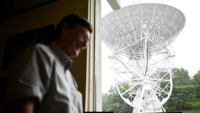 A radio telescope is seen in the distance at PARI with founder Don Cline in the foreground June 21, 2017.