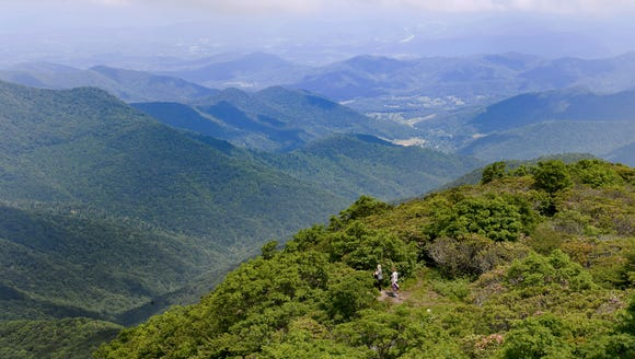 A pair of hikers make their way up to the Craggy Pinnacle