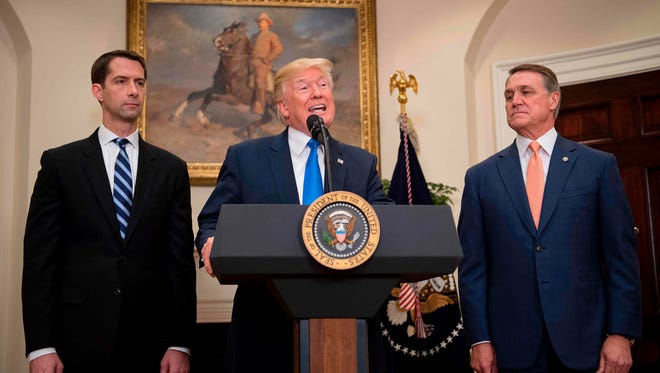 President Trump, flanked by Sens. Tom Cotton of Arkansas and  David Perdue of Georgia.