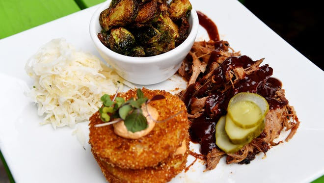 Farm to Fender Cafe's meat and three with Hickory Nut Gap pork, cajun fried brussle sprouts, jicama slaw and fried green tomatoes with chipotle pimento.