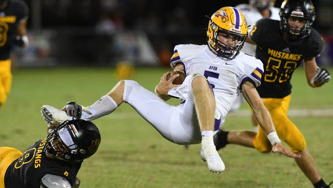 Avon QB Ryan Malloy is upended by Josef Johnson of Merritt Island (8) during Thursday's game at Disney's Wide World of Sports.