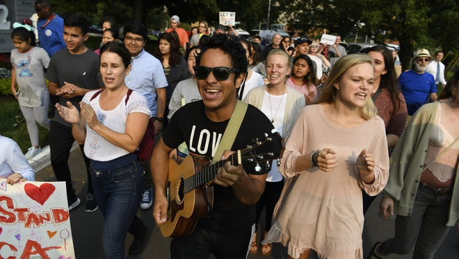 Gustavo Guerrero marches with a guitar during a rally in support of Deferred Action for Childhood Arrivals (DACA) on Tuesday, Sept. 5, 2017.