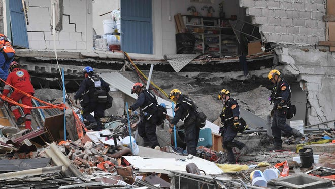 Rescue workers evacuate the place where they were working after a seismic alert sounded in Mexico City on Sept. 23, 2017, four days after the powerful quake that hit central Mexico.