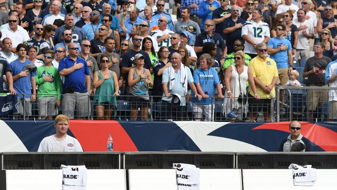 The Seahawks' bench is empty as fans stand during the national anthem Sunday, Sept. 24, 2017. Both benches were empty during the singing at Nissan Stadium.