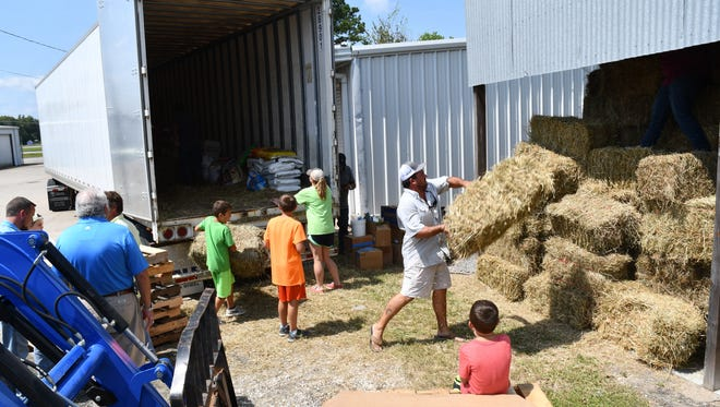 A truck of donated hay and other supplies from New Jersey is unloaded in Sour Lake, Texas. Hay and feed donations were valued at more than $1.3 million, according to Texas A&M AgriLife Extension economists.
