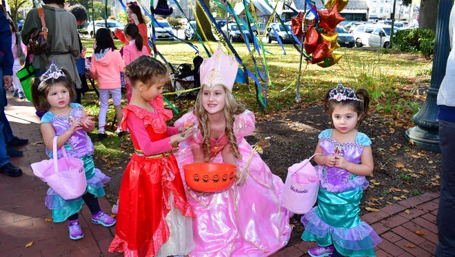 Juliana Nolan, the good witch of the Wizard of Oz, center, greets kids with candy.