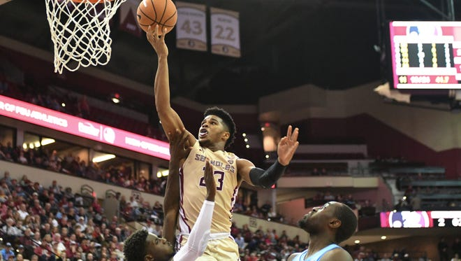 FSU freshman guard MJ Walker (23) scoring a layup over North Carolina defenders during the second half.
