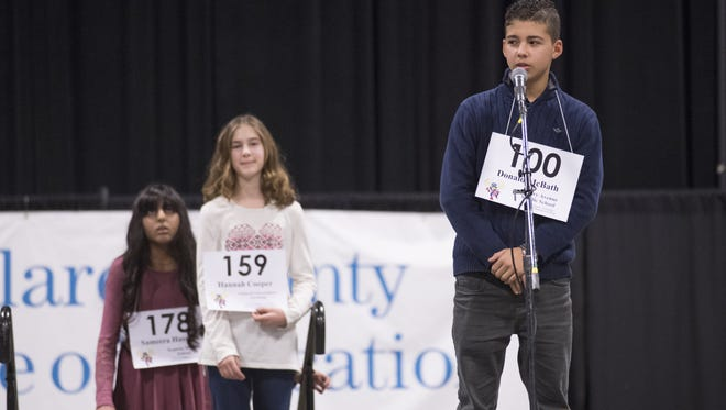 Donald McBath of Cherry Avenue School, right, spells during the 18th Annual Tulare County Spelling Championship at the Visalia Convention Center on Wednesday, February 22, 2017.