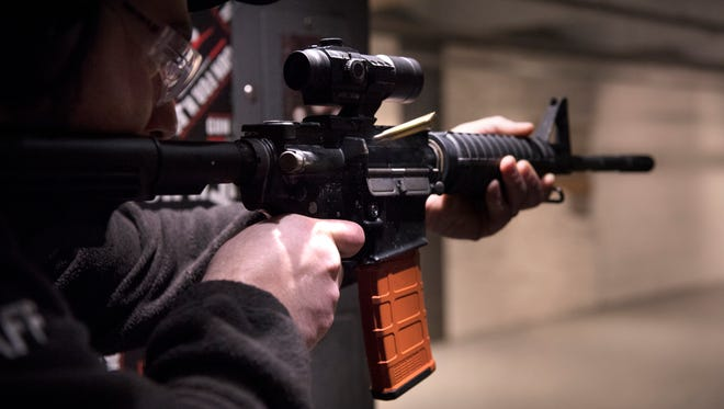Jimmy Grammenos, general manager and director of training at the Gun For Hire shooting range in Woodland Park, fires an AR-15-style semiautomatic rifle. The gun has become the weapon of choice for many — and, according to gun dealers and marketing experts, quite possibly the hottest-selling gun in America.