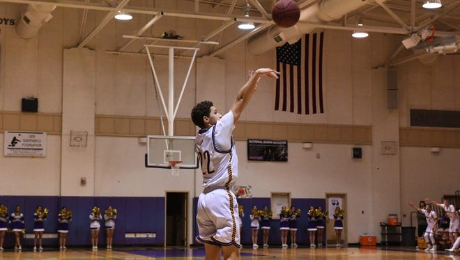Senior guard Jarrett Edria shoots from the three-point territory for the Cowboys in the second quarter.