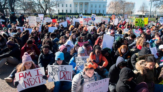 Thousands of local students sit for 17 minutes in honor of the 17 students killed last month in a high school shooting in Florida, during a nationwide student walkout for gun control in front the White House in Washington, DC, March 14, 2018.