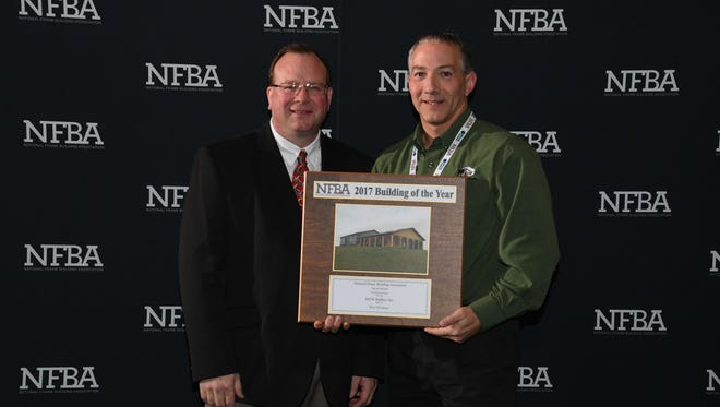 Doyle Pokorny is pictured receiving the NFBA Suburban Garages Building of the Year Award at the National Frame Building Association annual convention and trade show.