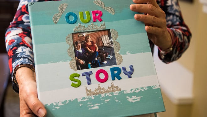 Kathy Kirkland holds the scrapbook she made with her mother, Joan Harrison, at a Cedar City, Utah, retirement home. Harrison gave Kirkland up for adoption 60 years ago, and the two were reunited in late 2017.