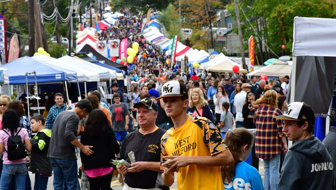 Aidan McDaniel, yellow shirt, has a baseball in his hands as part of West Milford baseball team, one of the tent vendors. Street Fair on Union Valley Road where it forks at Marshall Hill Road in West Milford on Saturday morning October 14, 2017.